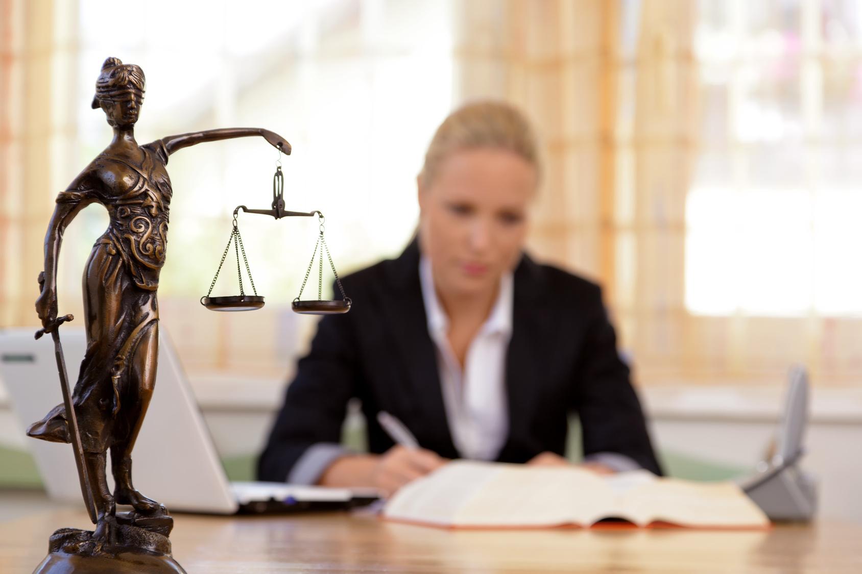 Statue Justitia auf dem Schreibtisch einer Rechtsanwältin für Verkehrsrecht